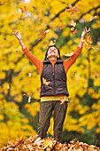 Hispanic woman throwing autumn leaves, Seattle, WA