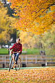 African woman riding bicycle in park in autumn, Seattle, WA