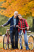 African couple standing with bicycles in park in autumn, Seattle, WA