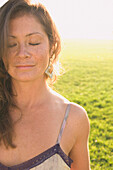 Portrait of woman in sunlit meadow, Kenneth Hahn State Park, CA