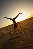 Mixed race woman doing cartwheel on beach, Santa Monica, CA