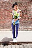 Mixed race woman holding bouquet on urban sidewalk