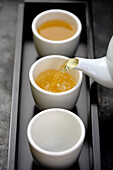 Green tea being poured from teapot into cups on tray, Santa Fe, New Mexico, United States