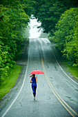 Caucasian woman running on remote road with umbrella, Bainbridge Island, Wa, USA