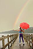 Caucasian woman in sportswear with red umbrella on pier catching rainbow, Bainbridge Island, Wa, USA