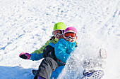 Mixed race girls sledding in snow, Seattle, WA, USA