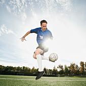 Caucasian soccer player kicking soccer ball, Ladera Ranch, California, USA