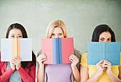 Women hiding behind books, Jersey City, New Jersey, USA