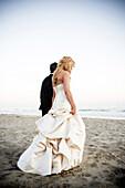 Bride and groom walking on beach, Santa Barbara, California, USA
