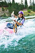 Caucasian teenager kayaking in river, Boise, Idaho, USA