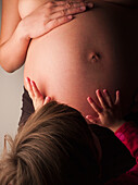 Child patting pregnant mother's stomach, New York, New York, United States