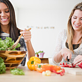 Teenage girls preparing salad together, Jersey City, New Jersey, USA