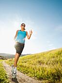 Pregnant Hispanic woman running in remote area, Aliso Viejo, California, USA