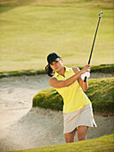 Mixed race woman hitting golf ball out of bunker, Mission Viejo, California, USA