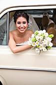 Hispanic bride sitting with bouquet in back of car, Zacatecas, Zacatecas, Mexico