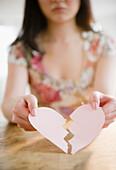 Korean woman holding torn paper heart, Jersey City, New Jersey, USA