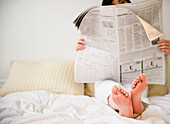 Korean woman reading newspaper in bed, Jersey City, New Jersey, USA