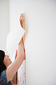 Korean woman putting wall paper on wall, Jersey City, New Jersey, USA