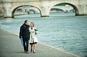Caucasian couple walking near city river, Paris, Paris, France