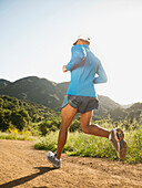 Mixed race man running on remote trail, Calabasas, California, United States