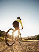 Mixed race woman riding on mountain bike, Calabasas, California, United States