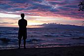 Caucasian man standing on beach viewing sunset, Kep, Kep, Cambodia