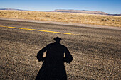 Shadow of cowboy on remote highway, Page, Arizona, United States