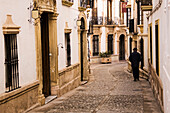 Man walking down cobblestone alley in quaint village, Carmona, Andalucia, Spain