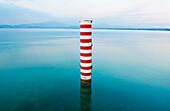 Red and white stripe pillar in tranquil lake, Lago Di Garda, Verona, United States