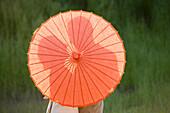 Caucasian couple standing behind parasol, South Jordan, Utah, United States