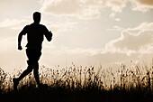 Caucasian man running at sunset, South Jordan, Utah, United States