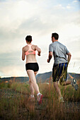 Caucasian couple running together on remote path, South Jordan, Utah, United States