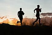 Caucasian couple running together at sunset, South Jordan, Utah, United States