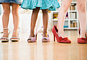 Girls trying on glamorous high-heeled shoes, Jersey City, New Jersey, USA