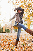 Caucasian woman playing in autumn leaves, Provo, Utah, USA