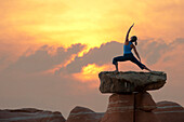 Caucasian woman practicing yoga on top of rock formation, Kanab, Utah, USA