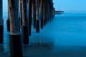 Ocean and dock pilings at beach, Ventura, California, United States