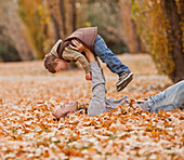 Caucasian father and son playing in autumn leaves, Provo, Utah, USA
