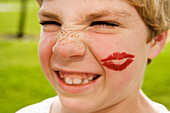Grimacing boy with lipstick kiss on face, Elk Grove, CA, USA