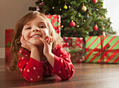 Caucasian girl laying on floor near Christmas tree, Lehi, Utah, USA