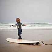 Caucasian boy practicing surfing on beach, Manhattan Beach, California, USA