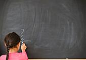 Mixed race girl doing math on blackboard, Jersey City, New Jersey, USA