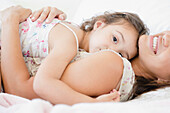 Mother and daughter laying on bed, Jersey City, New Jersey, USA