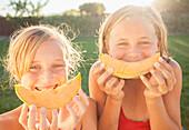 Caucasian girls eating cantaloupe, Lehi, Utah, USA