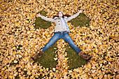 Caucasian woman making angel in autumn leaves, Alpine, Utah, USA
