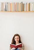 Hispanic girl reading under bookshelf, Jersey City, New Jersey, USA