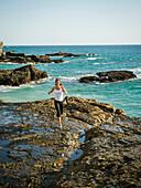 Mixed race woman running on rocky beach, Laguna Beach, California, USA