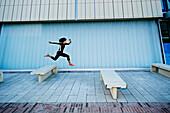Mixed race woman running on city street, Los Angeles, California, USA
