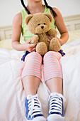 Korean girl holding teddy bear on bed