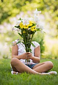 Mixed race girl holding bouquet of flowers in grass, Huntington Station, New York, USA
